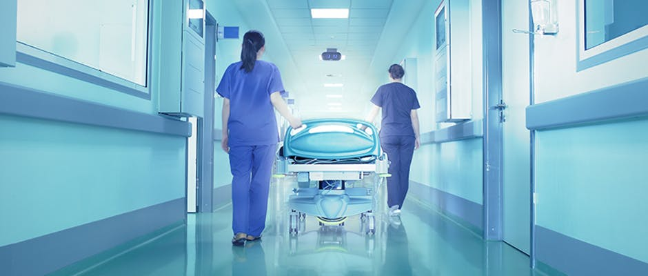 Two nurses walking down a hallway with a stretcher after a hospital room has been cleaned
